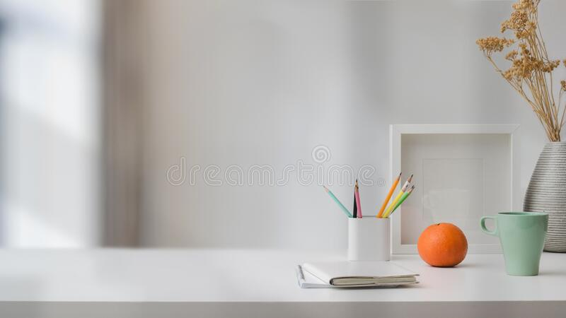 Close up view of  workspace with copy space, stationery, coffee cup, and decorations on white table with blurred background. Close up view of modern workspace stock image