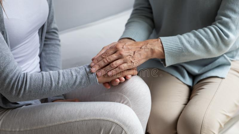 Closeup view mom stroking hands of adult grownup daughter stock photography