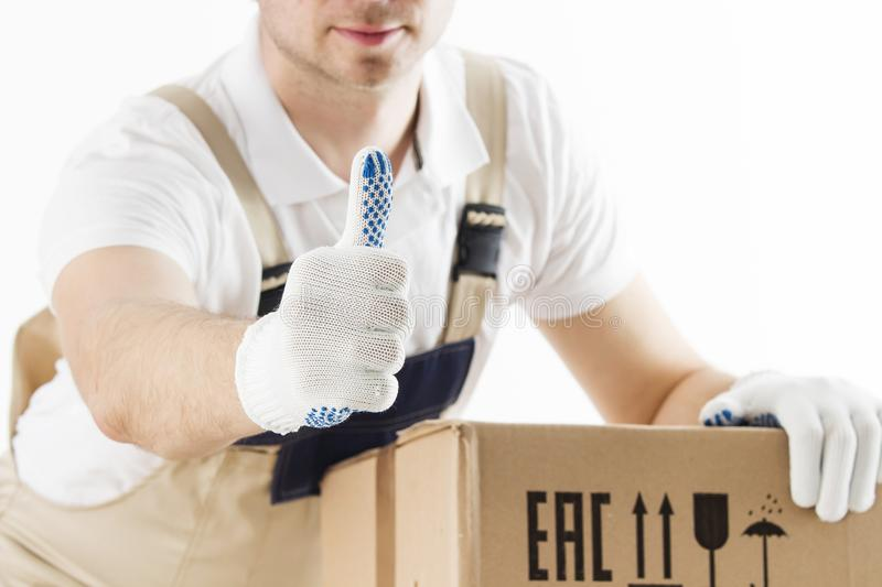 Close-up view of mover in uniform showing thumb up with cardboard boxes on white background. Relocation services worker royalty free stock images