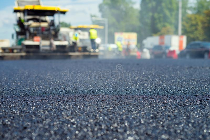 Close up view on the new asphalt road on which special equipment is working. Blurred photo of construction site. stock image