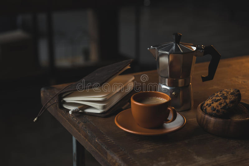 Close-up view of notebook with pencil, cup of coffee, moka pot and chocolate chip cookies stock photos