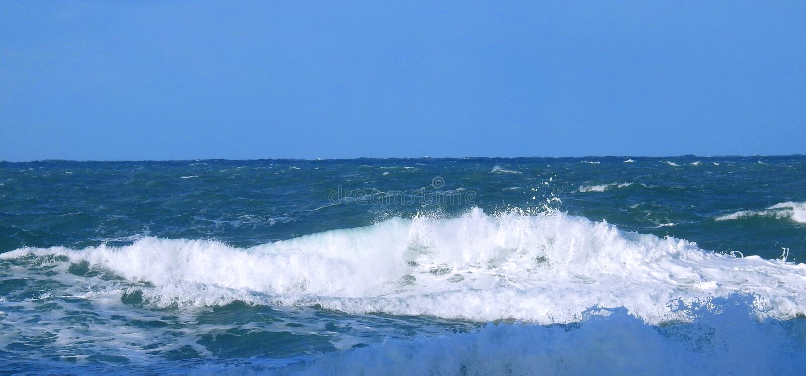 Close up view of an ocean wave with white foam stock image