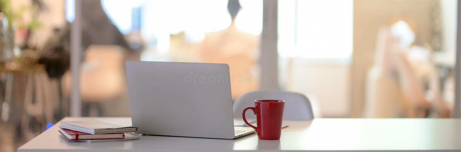 Close up view of office desk with blank screen laptop, notebook, coffee cup and copy space in glass partition room. Close up view of office desk with blank royalty free stock photos