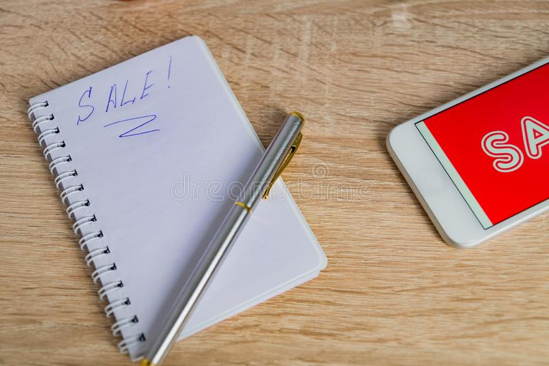Close up view of office desk with white smartphone with sale text, note and pen. Technology business online shopping concept.  stock photography