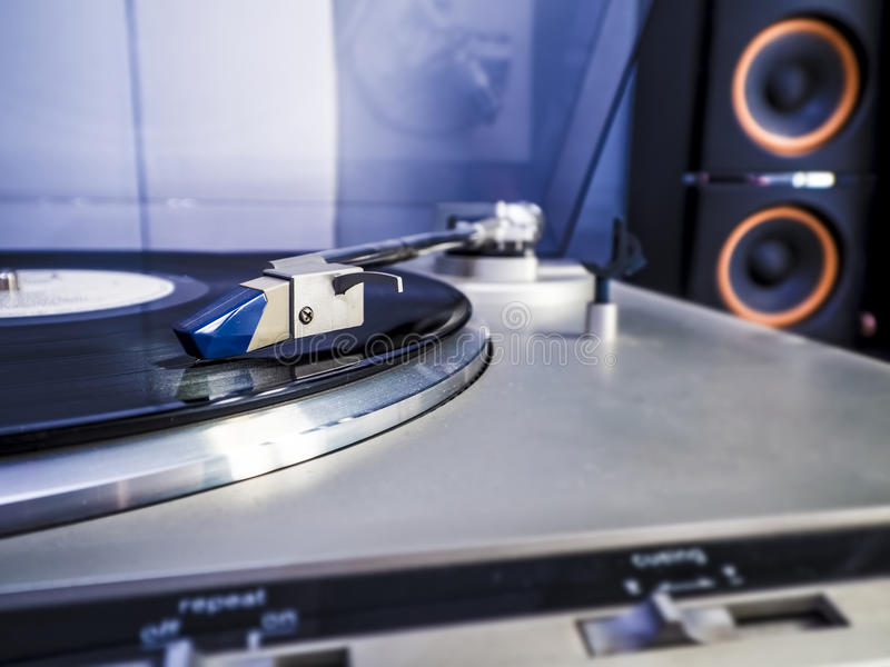 Close up view of old fashioned turntable. Playing a track from black vinyl with light bluish interior lightning stock image