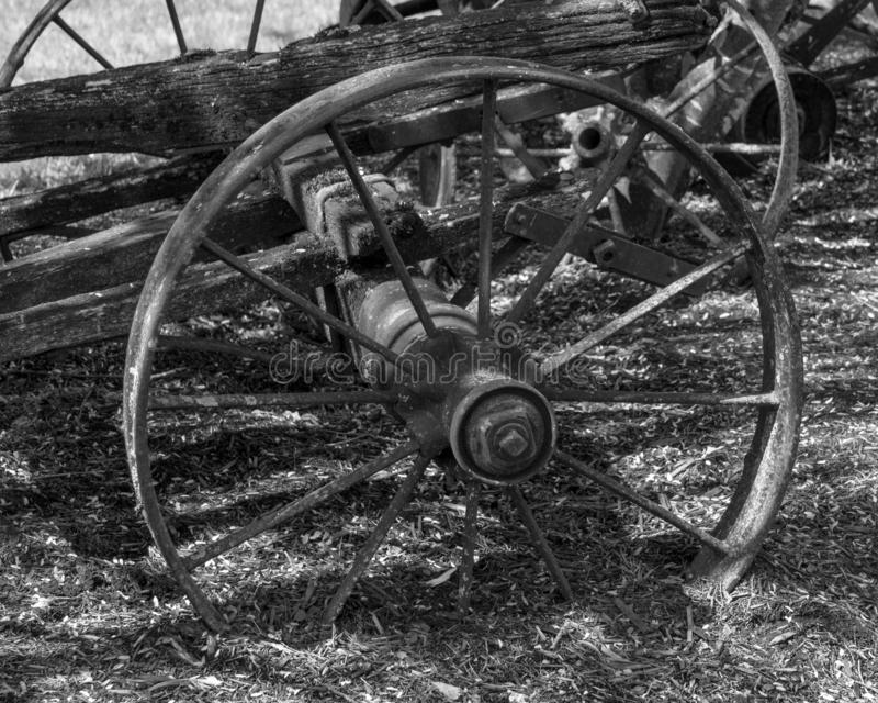 Close up view of the old metal wheel of the old wooden cart standing in a countryside. Wagon, antique, carriage, rural, rustic, western, aged, circle, farm stock photo