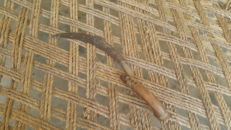 Close-up view of an old sickle reaping-hook on the bed surface. Close-up view of an old sickle bagging hook or reaping-hook on the bed surface. Traditional hand stock photos