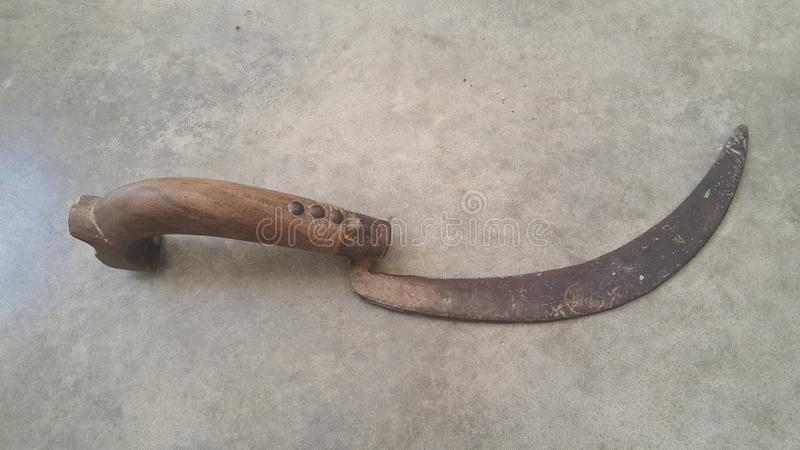Close-up view of an old sickle & x28;reaping-hook& x29; on the concrete surface. Close-up view of an old sickle & x28;bagging hook or reaping-hook& x29; on the stock photos