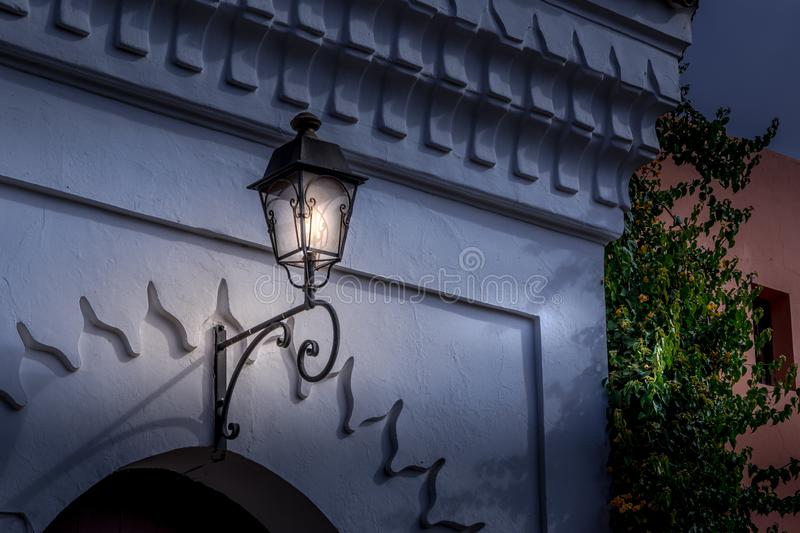 Close up view of an old traditional street lamp hanging over city entrance. Night in Marrakech, Morocco stock photography
