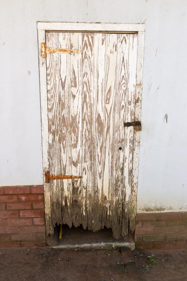 A Damaged Outside Shed Door. A close up view of a old white outside shed door that has rusted hindges, and locks and the wood at the bottom is rotten and been stock photos
