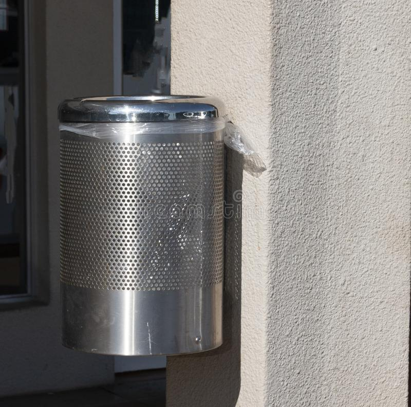 A Dirty White Post Box. A close up view of a open sliver steel outside dusbin bolted to a wall with a plastic bag lining royalty free stock photos