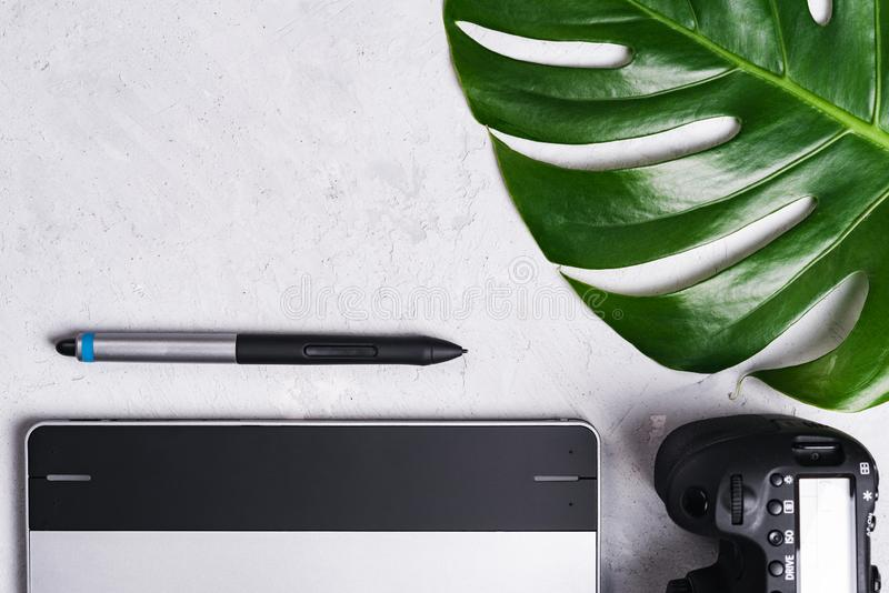 Close-up view of photographer`s of graphic designer`s workplace. Tablet, stylus, camera, monstera green leaf.  royalty free stock photos