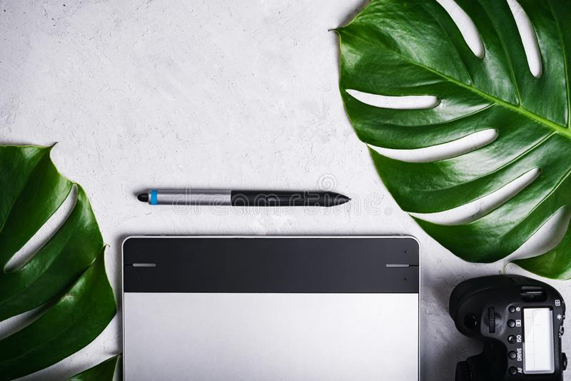 Close-up view of photographer`s of graphic designer`s workplace. Tablet, stylus, camera, monstera green leaf.  royalty free stock photography