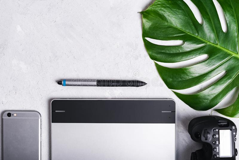 Close-up view of photographer`s of graphic designer`s workplace. Tablet, stylus, camera, smartphone, monstera green leaf.  royalty free stock image
