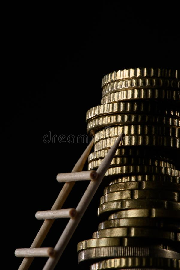 Close up view of pile of coins with little wooden ladder. Isolated on black stock images