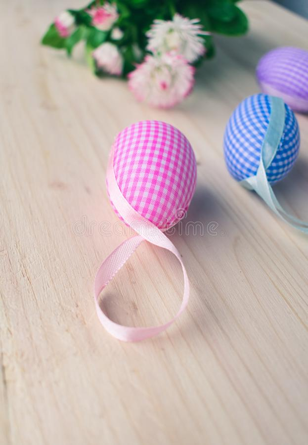 Close up view of pink and blue checkered Easter eggs decorations and white and pink daisies on pale wooden background stock images