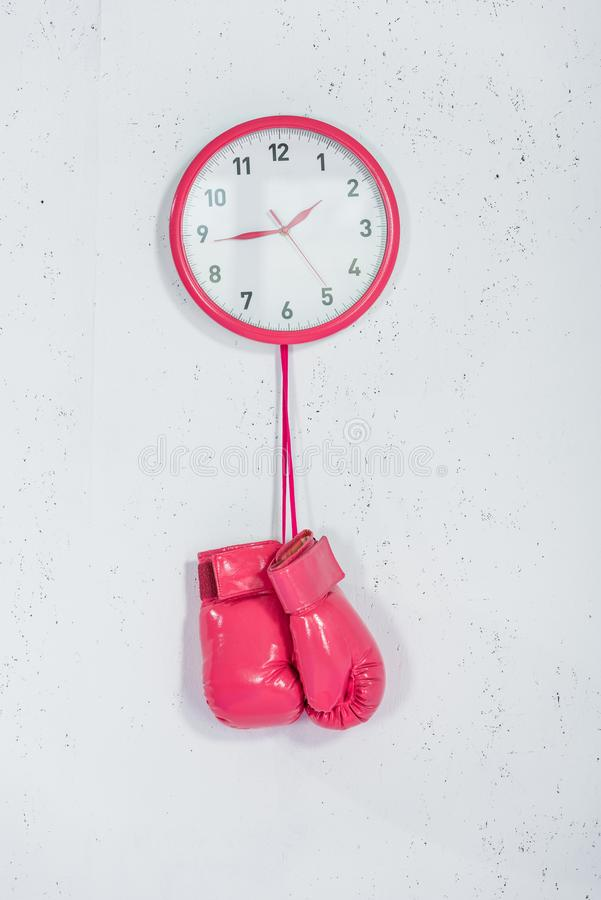 Close-up view of pink boxing gloves hanging at wall clock. On white stock photos