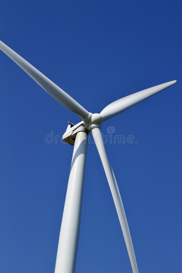 Close up view of the propellers on a giant wind power turbine with blue sky background stock image