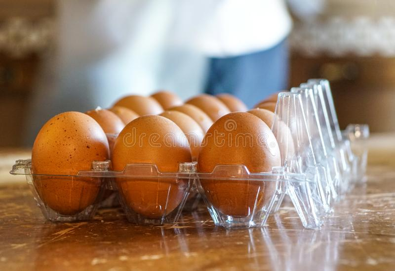 Close-up view of raw chicken eggs in egg box on wooden background . royalty free stock photo