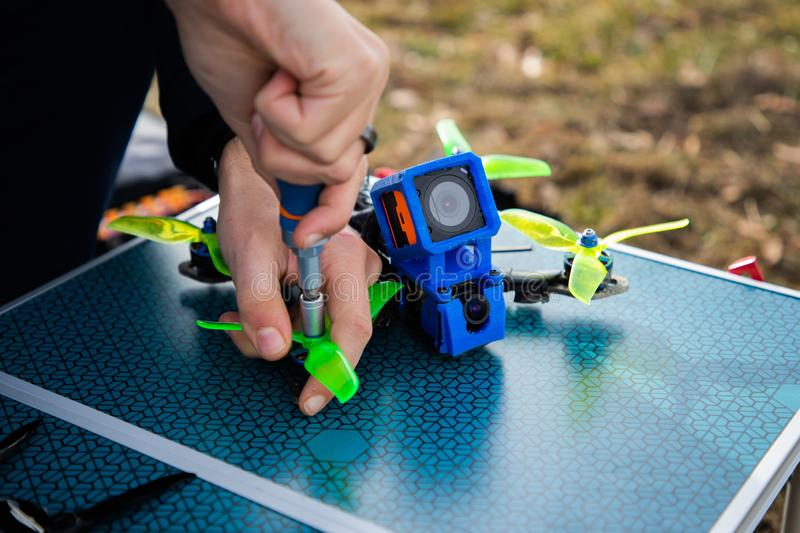 Close up view of a razing drone being repaired. Hand repairing a racing drone in a table with copy space, remote, propeller, outdoors, blue, wireless, multirotor stock images