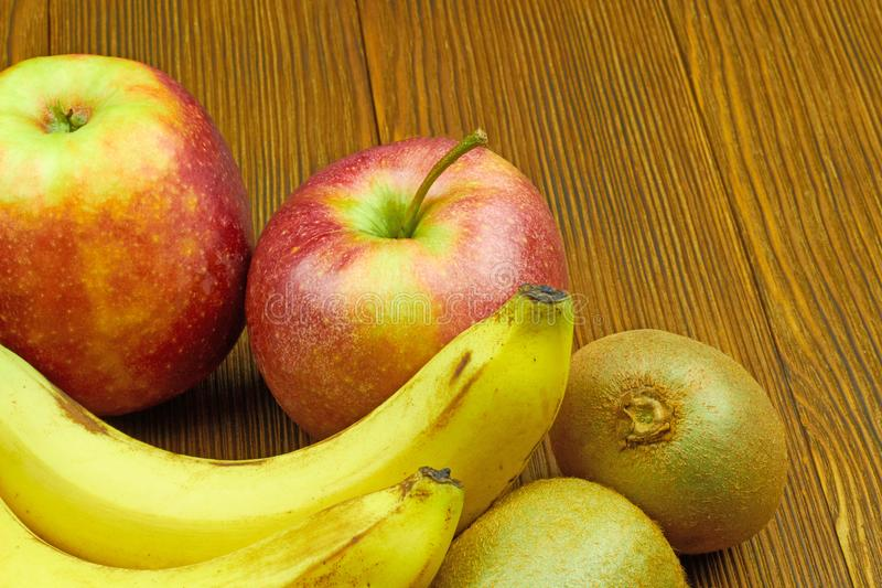 Close up view of red apples, bananas and kiwi on wooden background. Still life of fresh fruits stock photo
