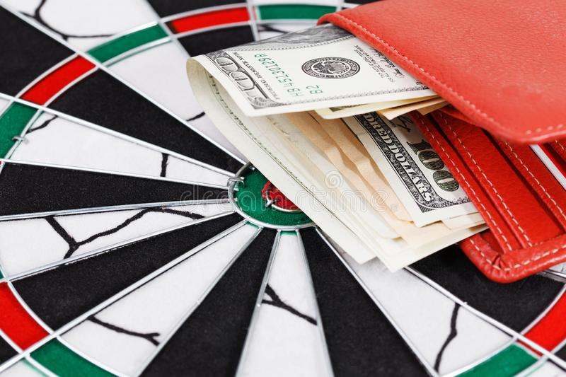 Close up view of red arrow and one hundred dollar bill on dart board. royalty free stock photo