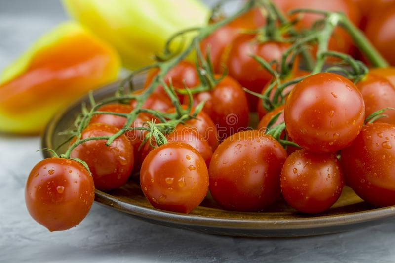 Close up view of red cherry tomatoes bunch in a plate and yellow sweet pepper on light background royalty free stock image