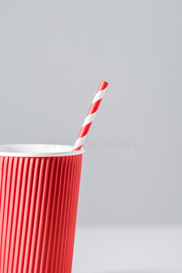 Red paper cup with drinking straw isolated on grey royalty free stock photos