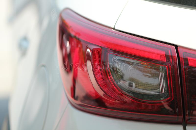 Close up view of red rear tail light of white car stock images
