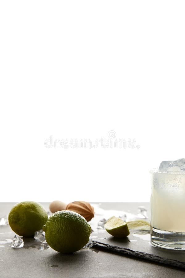 close up view of refreshing sour caipirinha cocktail with lime on tabletop on white stock photo