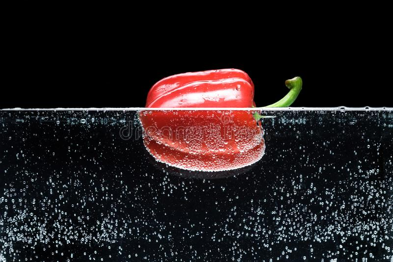 Close up view of ripe red bell pepper in water. Isolated on black stock image