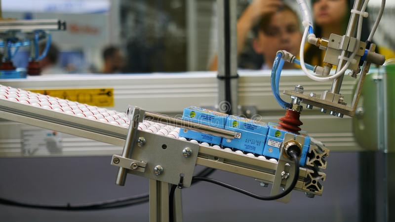 Close-up view of robotic machine sorting the juice boxing at the robotics forum exhibition and blurred figures of. Children on the background. Robots and royalty free stock image