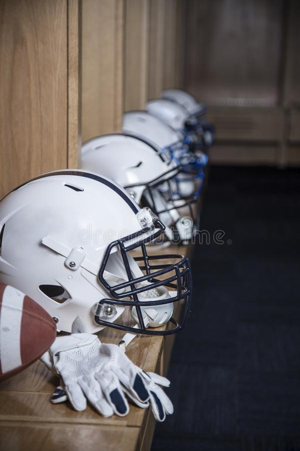 Close up view of a row of American football helmets sitting in a locker room before an football game. Gloves and a football also s royalty free stock photo