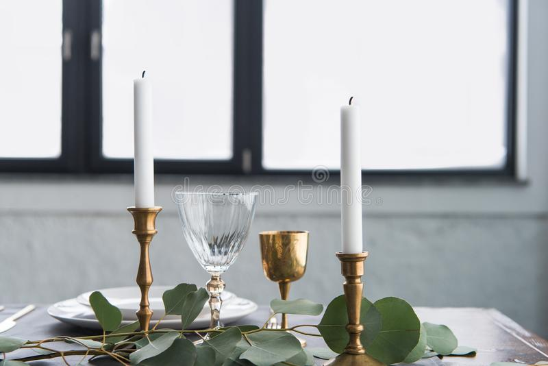 Close up view of rustic table arrangement with wine glasses, eucalyptus, candles in vintage candle holders and empty plates stock images