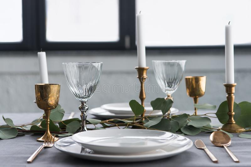 close up view of rustic table setting with wine glasses, eucalyptus, vintage cutlery, candles in candle holders and empty plates stock image