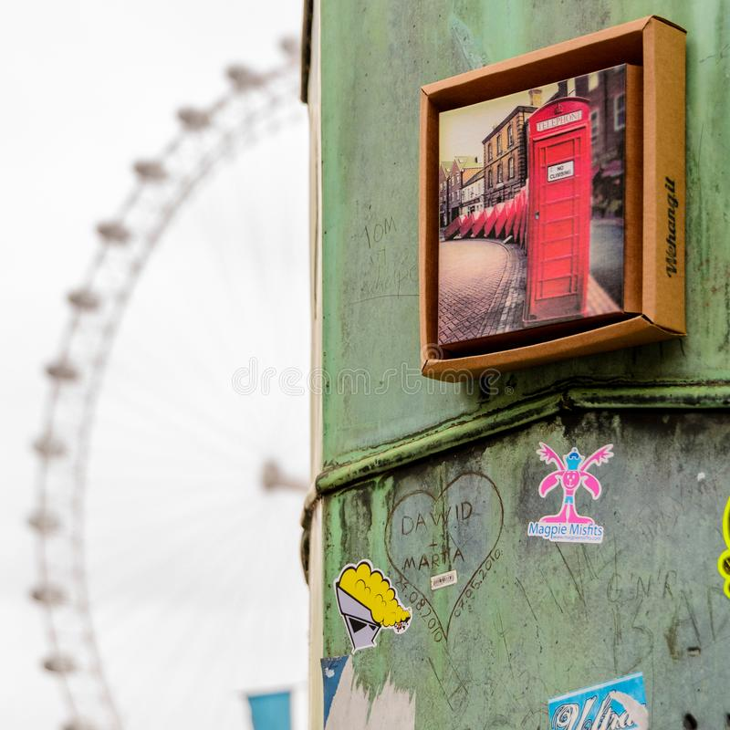 Close up view of a rusty metal column with stickers and a red phone booth photo on it with the London Eye on the background. royalty free stock images