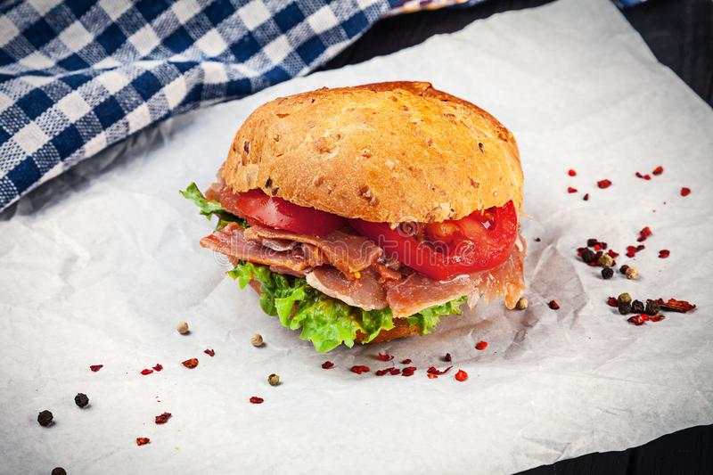 Close up view on Sandwich with prosciutto, lettuce, tomato on white background with copy space. Fast food. Snack. Food for lunch royalty free stock photography
