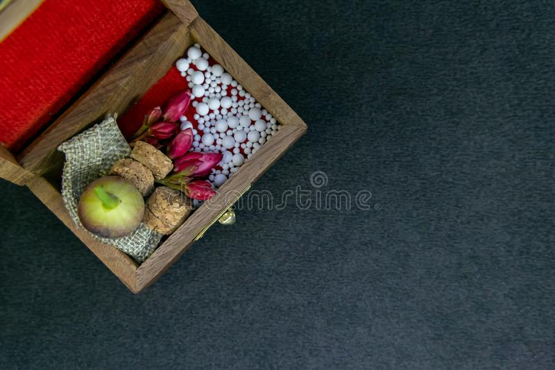 Close up view of scattered homeopathic pills with pink flowers, wild fruit, bottle's cork and burlap in wooden old box on dark stock image