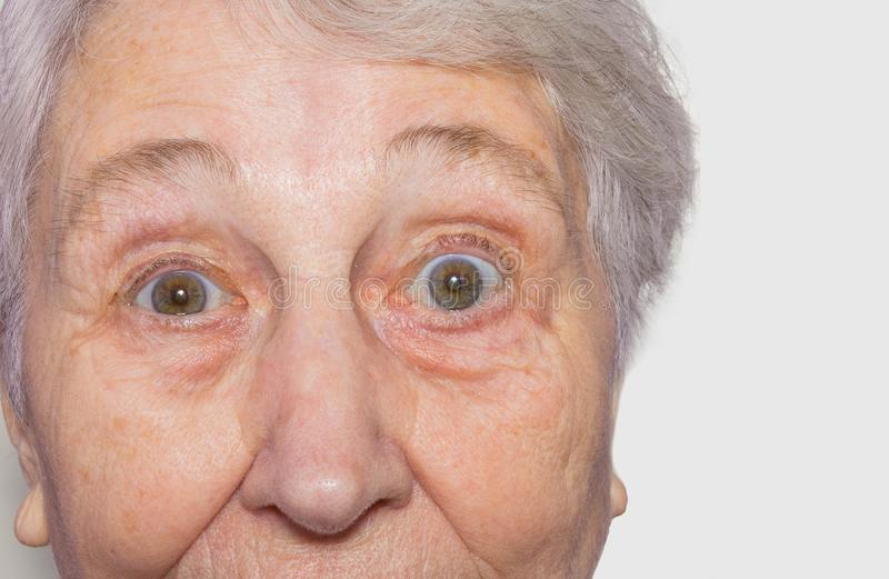 Close up view of senior woman`s face on white background. Concept surprised old woman and facial emotions stock photography