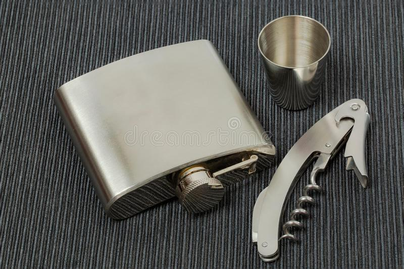 Close up view of set of steel flask, can opener and steel shot glass. Beautiful backgrounds. Steel backgrounds.  stock photography