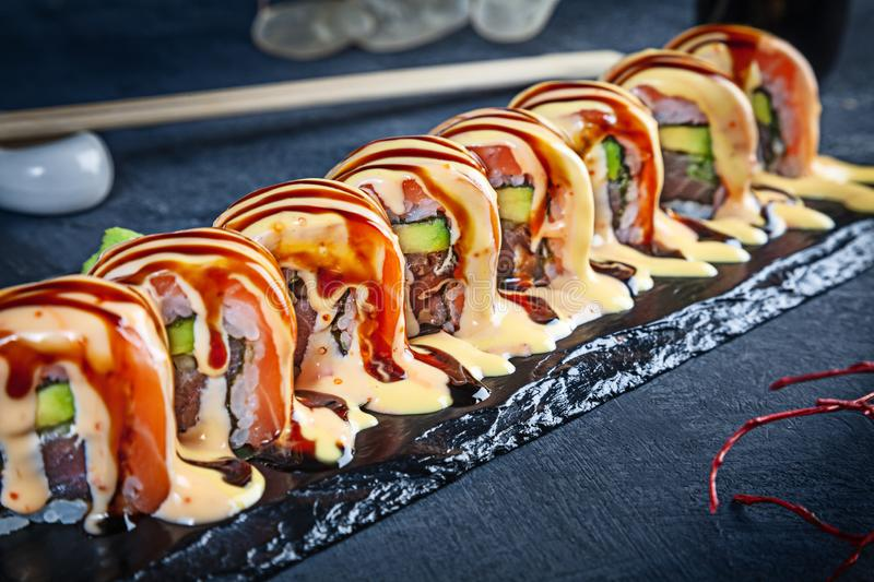 Close up view on set of sushi roll. California spicy roll with salmon served on black stone on dark background. Japanese cuisine. stock photos