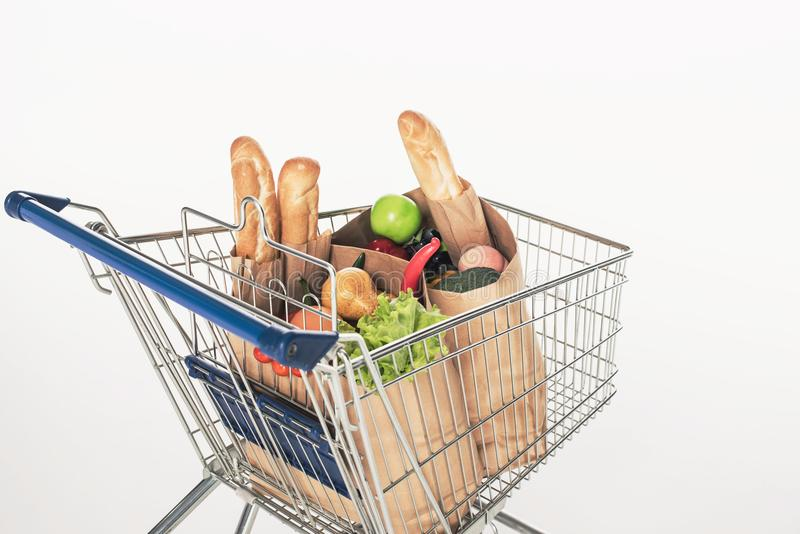 Close up view of shopping cart with paper packages full of grocery. Isolated on white stock images