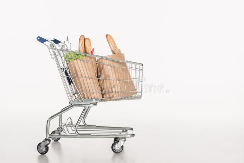 Close up view of shopping cart with paper packages full of grocery. On white stock photo