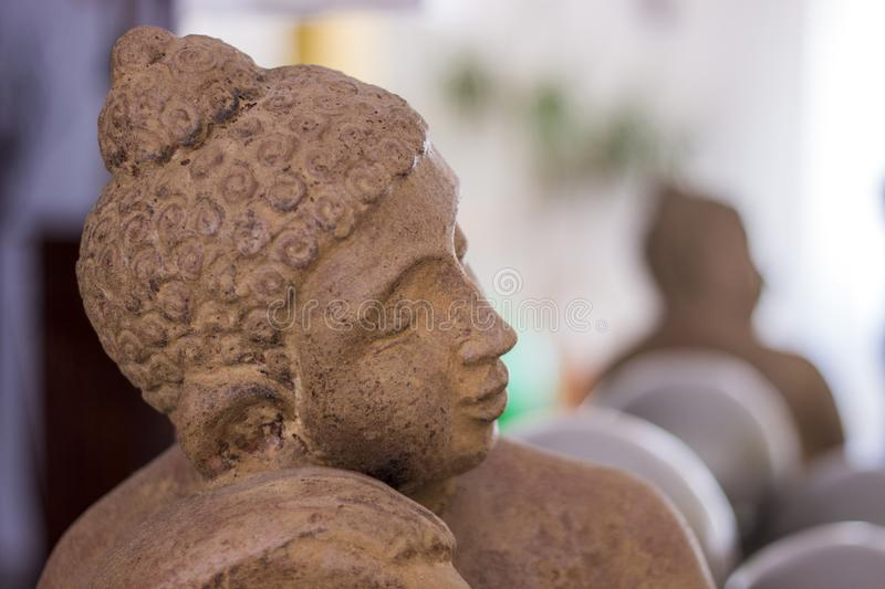 Small brown Buddha statue. Close up view of a small brown Buddha statue dreaming stock photos