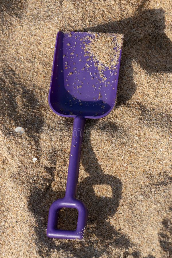 A Small Purple Spade. A close up view of a small purple spade in the beach sand on a beautiful sunny summers day royalty free stock photo