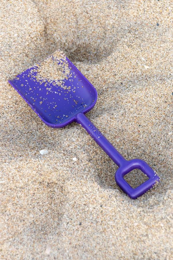 A Small Purple Spade. A close up view of a small purple spade in the beach sand on a beautiful sunny summers day stock photo
