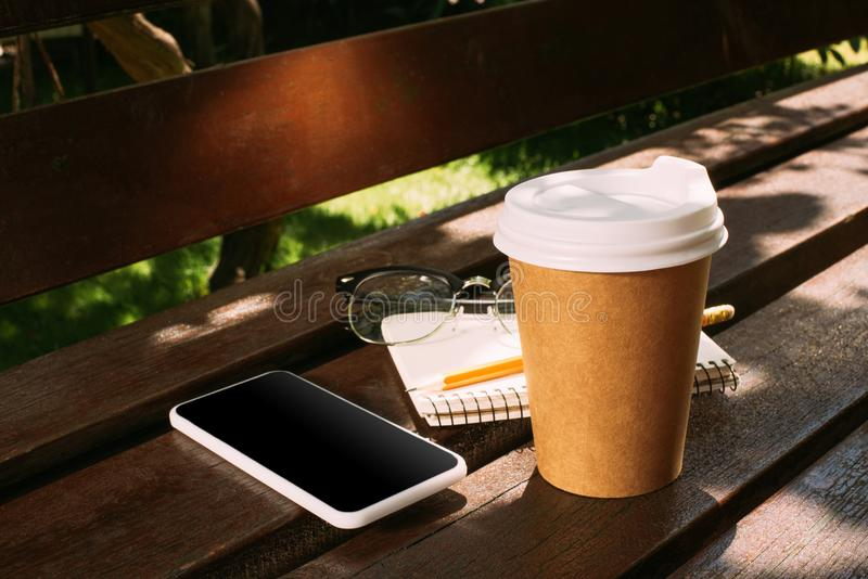 Close up view of smartphone, notebook, eyeglasses and coffee to go. On wooden bench stock images