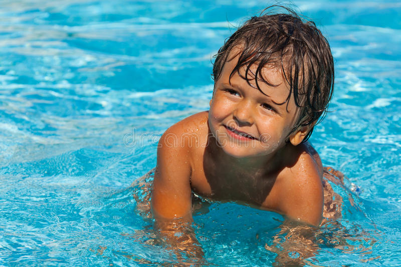 Close up view of smiling boy in swimming pool. Looking to the left stock image