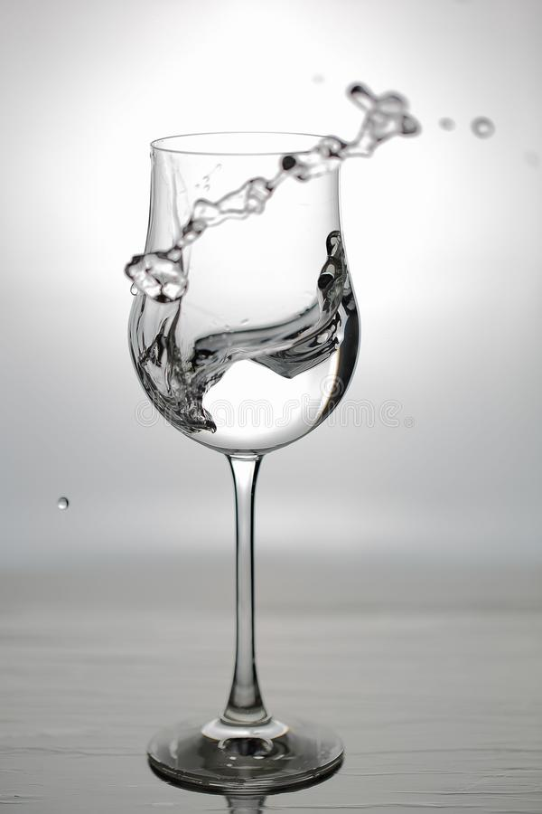 Close up view of splashing water in glass isolated. Black and white. Beautiful backgrounds royalty free stock photography