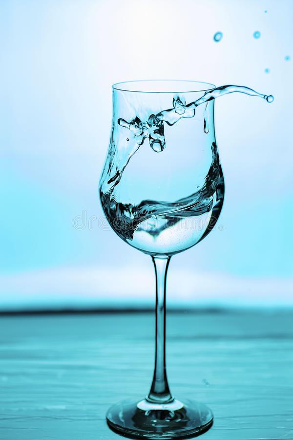 Close up view of splashing water in glass isolated. Blue / turquoise background. stock image
